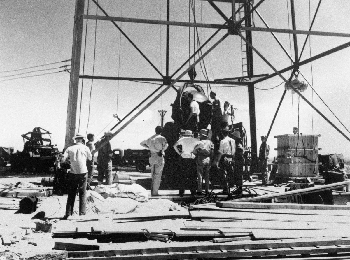 In this July 6, 1945, photo, scientists and other workers rig the world's first atomic bomb to raise it up onto a 100 foot tower at the Trinity bomb test site near Alamagordo, N.M. The president of the Navajo Nation and New Mexico residents who live downwind from the site of the world's first atomic blast are among those seeking recognition and compensation from the U.S. government for people affected by uranium mining and nuclear testing carried out during the Cold War. A congressional subcommittee was taking testimony Wednesday, March 24, 2021, about who should be eligible under the Radiation Exposure Compensation Act. (AP Photo/File )