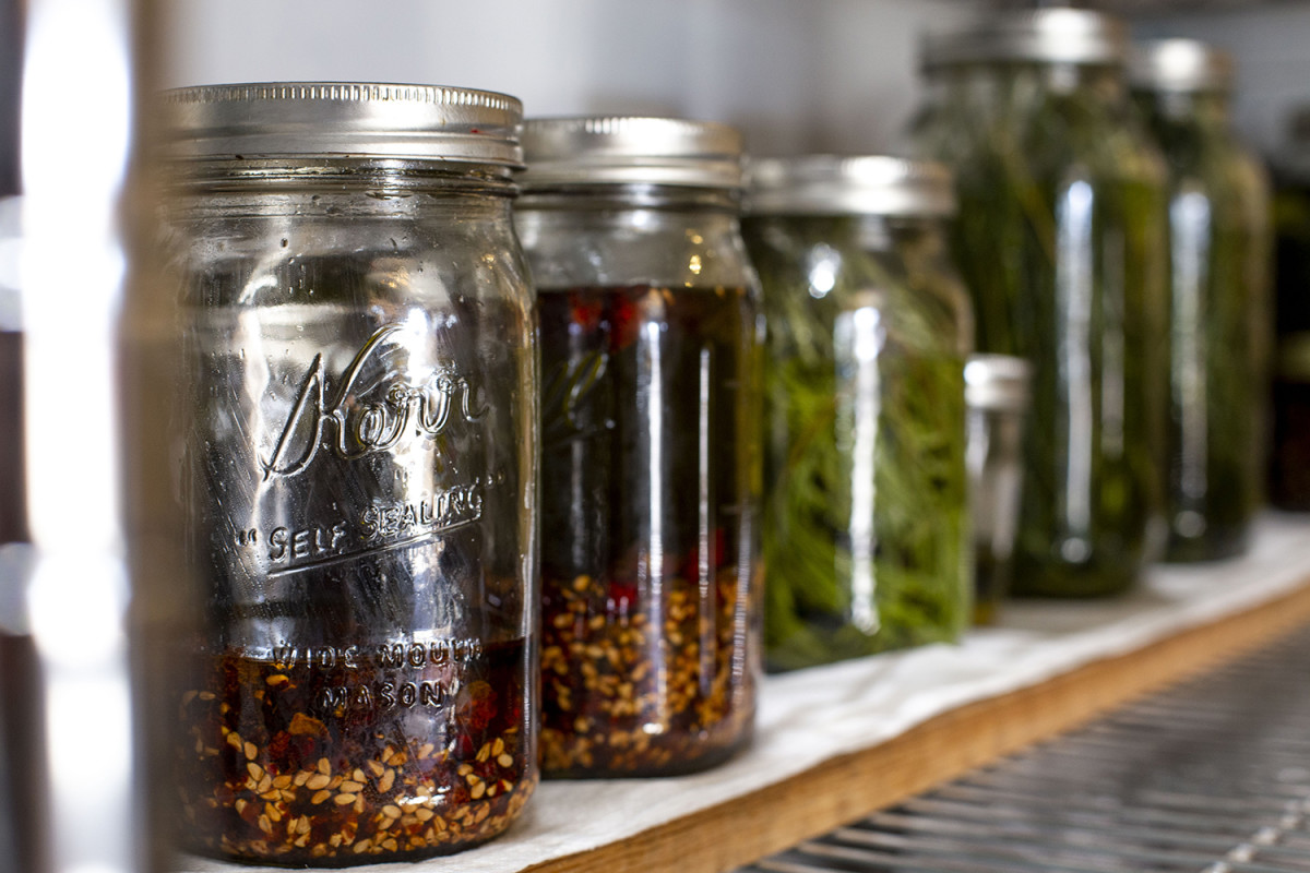 Jars of rose hips and sweetgrass sit on shelves. These plants are used for creating teas and syrups for Sakari Botanicals. (Photo by Jessica Douglas)