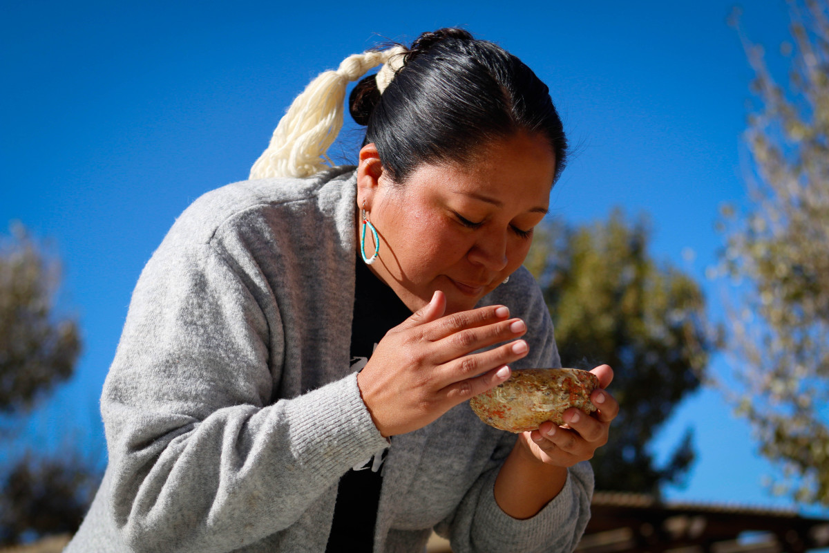 Nicolle Gonzales performs a smudging ceremony at doula training in Window Rock on Thursday, Oct. 24, 2019. Smudging cleanses the body by burning herbs and plants in a shell and fanning the smoke around a person, like a smoke bath. Gonzales is a nurse midwife and the founder and executive director of Changing Woman Initiative in Santa Fe, New Mexico. (Photo by Delia Johnson/Cronkite News)