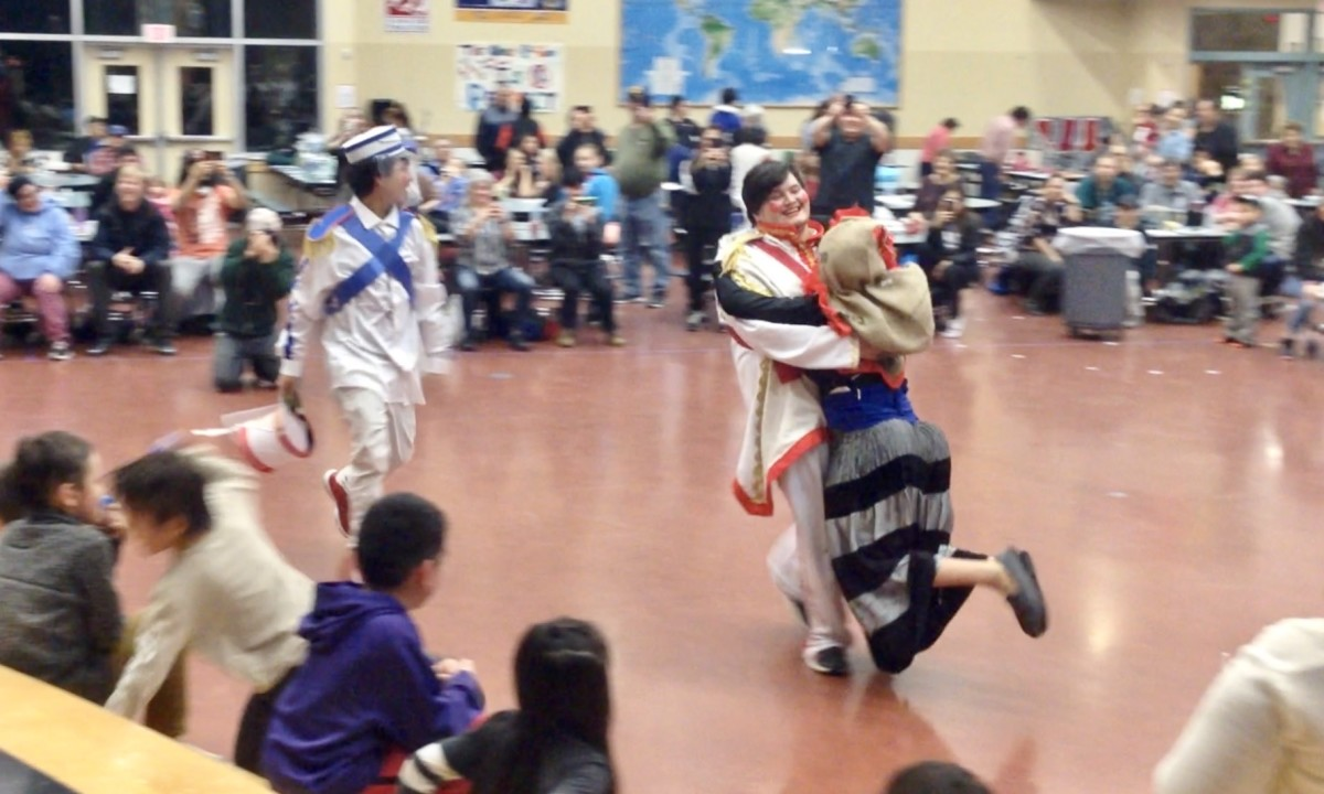 One of the Old Women (played by a man) gets carried off stage by the New Year, followed by the MP. (Photo by Joaqlin Estus)