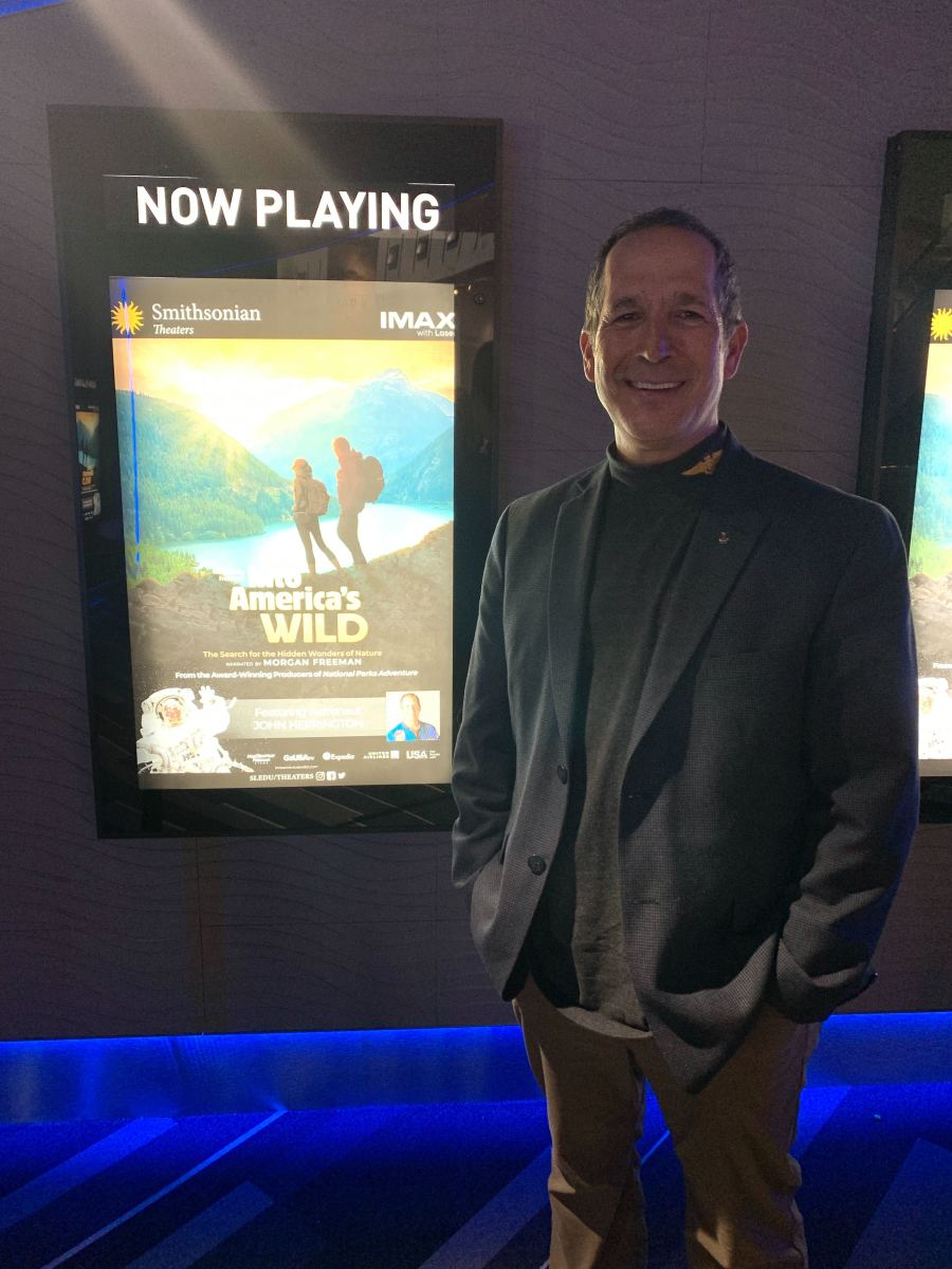 John Herrington, Chickasaw and the first Native American to travel in space, with his film poster behind him and in front of the Lockheed Martin IMAX Theater at the Smithsonian National Air and Space Museum in Washington, D.C. (Photo by Jourdan Bennett-Begaye)