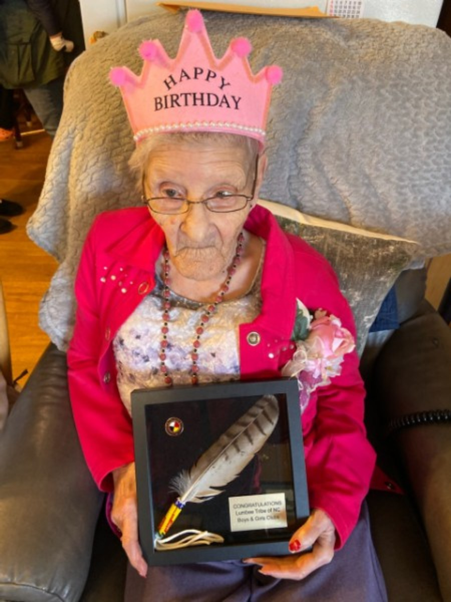 Dorothy Locklear Clark  holds a gifted feather from the Lumbee Boys and Girls club. (Photo James Locklear)