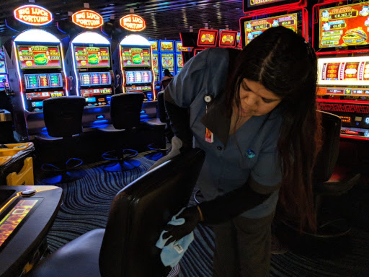 Adria Hill, Salt River Pima Maricopa, sanitizing the slot area and chair at Talking Stick Casino. (Photo by Patty Talahongva, Indian Country Today)