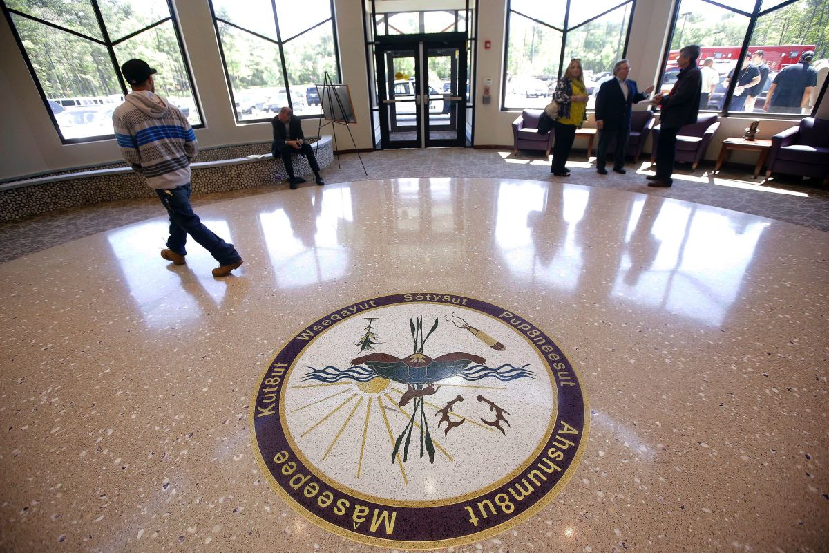 In this May 29, 2014, file photo, people stand in the lobby of the newly constructed Mashpee Wampanoag Tribe's Community Government Center in Mashpee, Mass., on Cape Cod. The tribe says an unfavorable decision from the U.S. Interior Department in 2018 on its tribal reservation status would effectively shut down some of it's government operations. (AP Photo/Stephan Savoia, File)