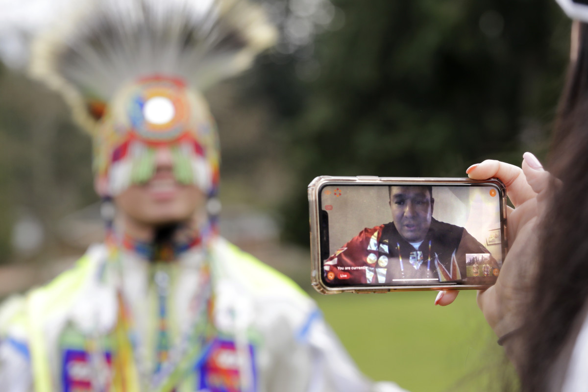 In this photo taken Saturday, April 4, 2020, moderator Whitney Rencountre, a Crow Creek Dakota tribal member, is seen on a screen from Rapid City, S.D., as he talks with a dancer during a live-streamed powwow. (AP Photo/Elaine Thompson)