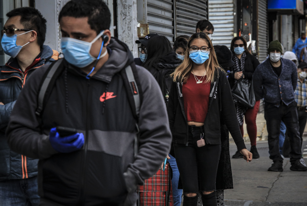 People in Brooklyn's Sunset Park, a neighborhood with one of the city's largest Mexican and Hispanic community, wear masks to help stop the spread of coronavirus while waiting in line to enter a store, Tuesday May 5, 2020, in New York. A poll found that 61 percent of Hispanic Americans say they've experienced some kind of household income loss as a result of the COVID-19 outbreak. (AP Photo/Bebeto Matthews)
