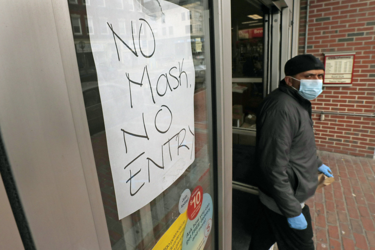 In this April 28 photo, a masked shopper walks past a sign taped to the front door of a CVS Pharmacy, requesting patrons wear masks if they intend on shopping inside due to the COVID-19 virus outbreak, in Chelsea, Mass. (AP Photo/Charles Krupa, File)