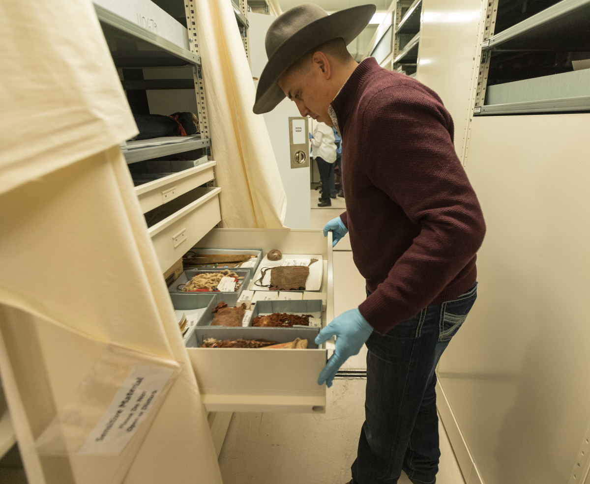 Aaron Brien examines different cultural artifacts in the catalogs room of the Field Museum. Brien worked as a cultural advisor for the exhibit and that inspired him to write a book about the history of the shields. (Photo by Trevor Reid)