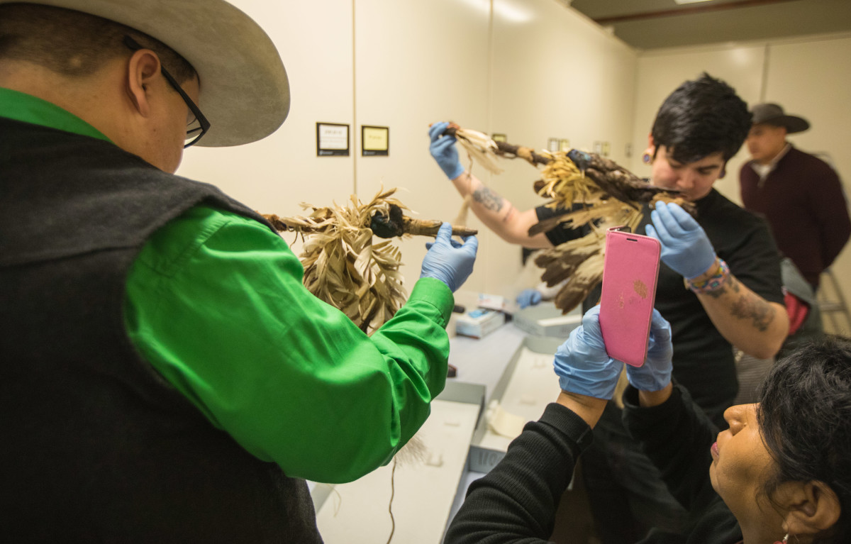 Riley Singer, left, and Elias Not Afraid, right, hold traditional tobacco society pipes of the Apsáalooke people, a few of the hundreds of historical items held by the Field museum in their artifact catalog rooms. (Photo by Trevor Reid)