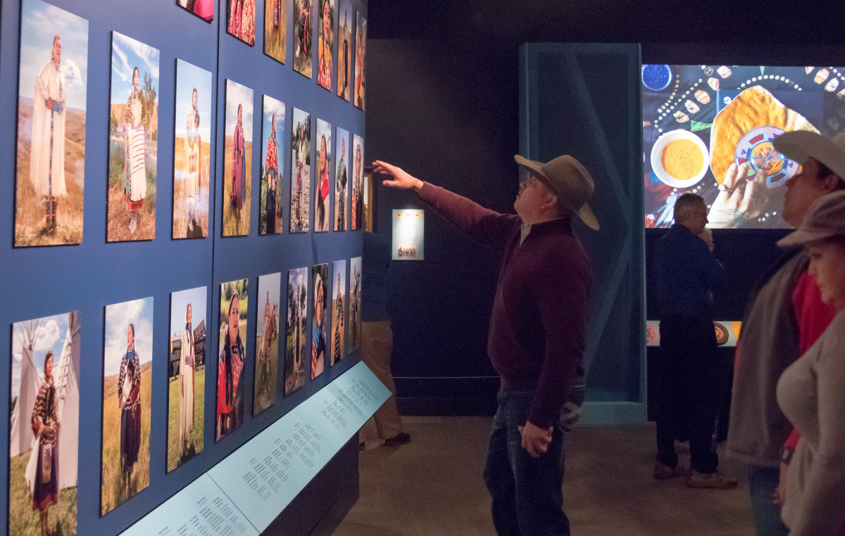 "Aaron Brien walks through the Field Museum's ""áalooke Women and Warriors"" exhibit on March 11, 2020, stopping to view one of the portraits on display. (Photo by Trevor Reid)"