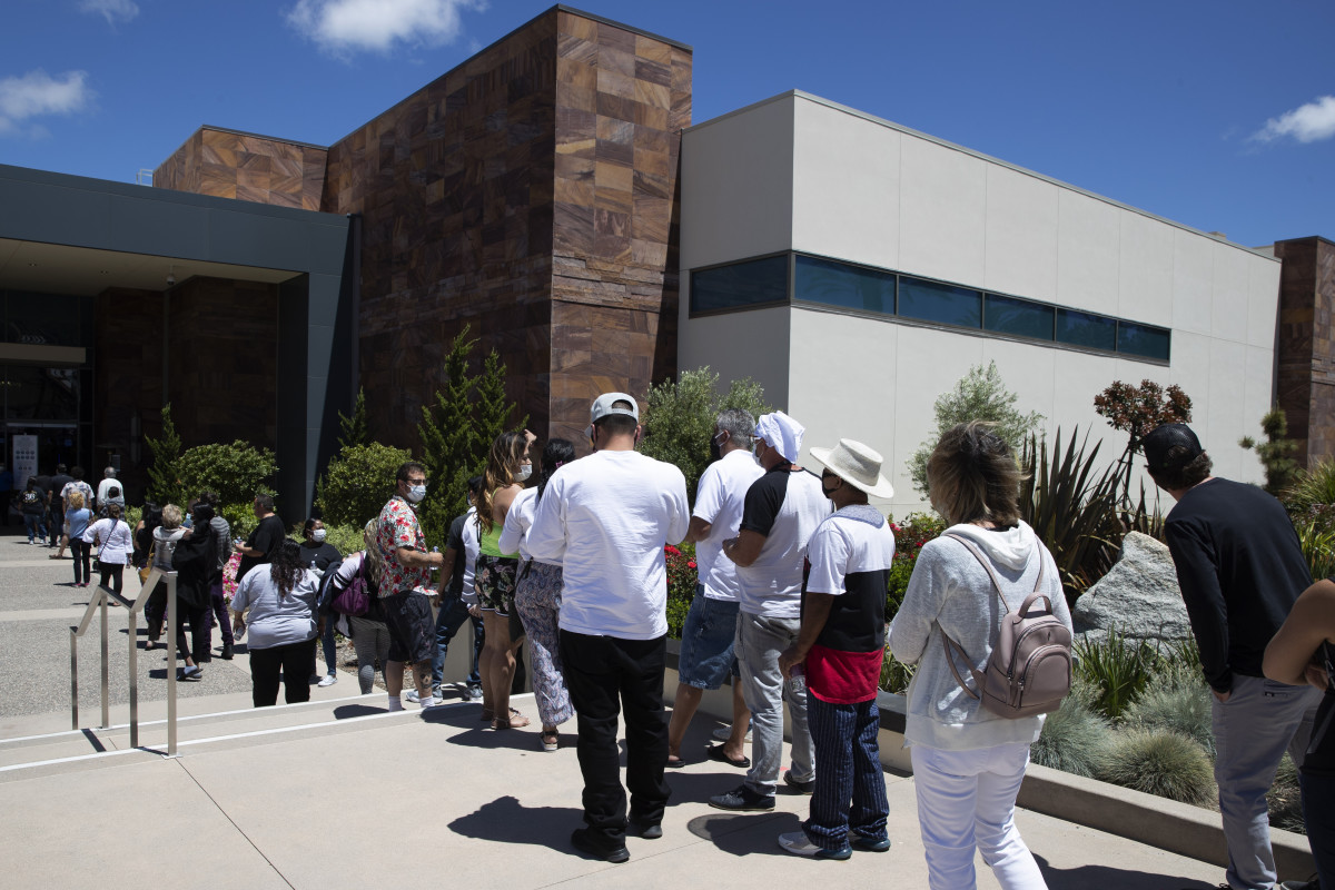 People wait in line at the entrance to the Viejas Casino and Resort as it reopens Monday, May 18, 2020, in Alpine, Calif. The casino is one of several on tribal lands in Southern California set to reopen this week. (AP Photo/Gregory Bull)