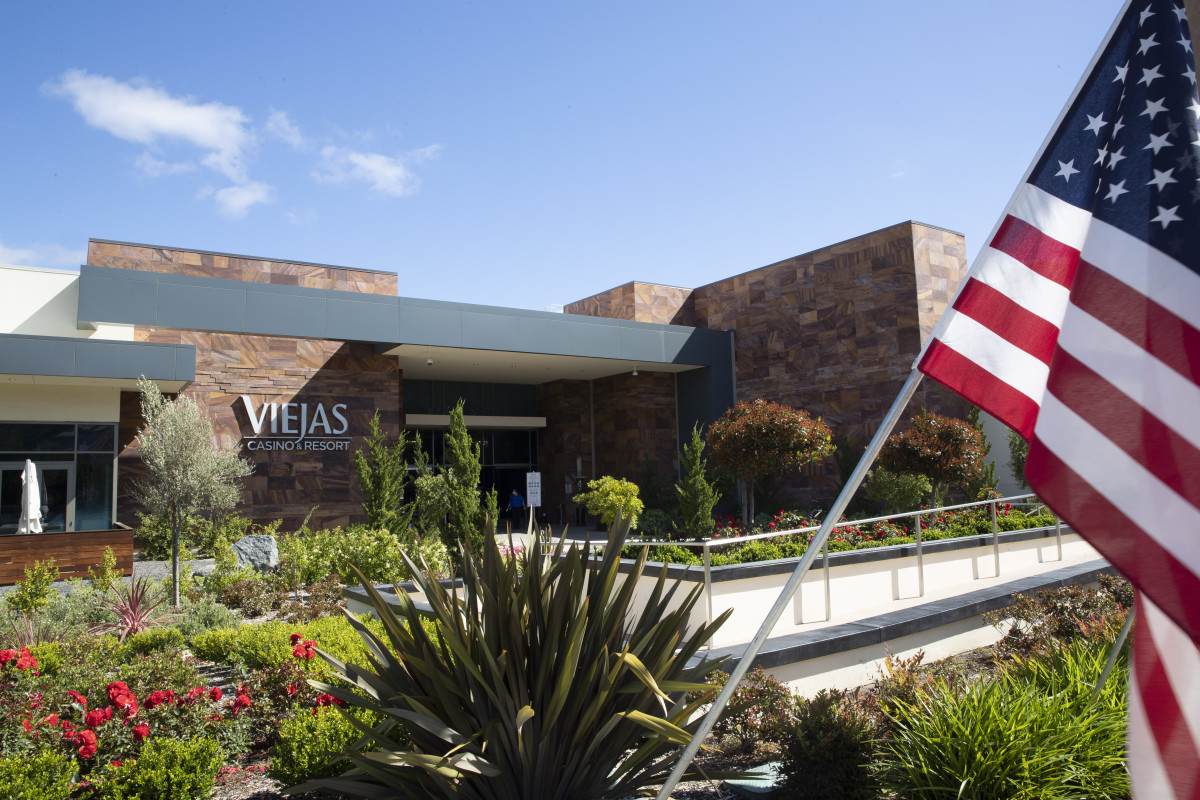A U.S. Flag waves at the entrance to the Viejas Casino and Resort as it reopens Monday, May 18, 2020, in Alpine, Calif. The casino is one of several on tribal lands in Southern California set to reopen this week. (AP Photo/Gregory Bull)