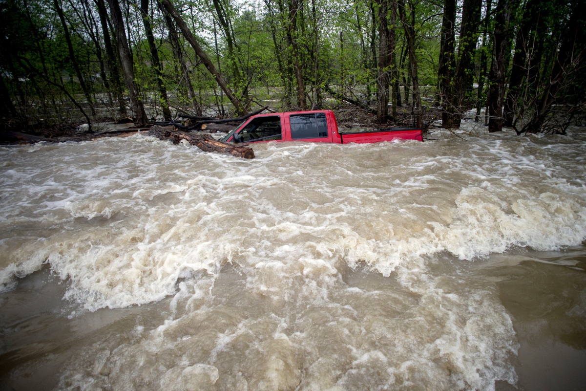 Tittabawassee Fire and Rescue rescued the driver from this red pickup truck on Norh Gleaner Road near its intersection with Tittabawassee Road on Tuesday, May 19, 2020 in Saginaw County, Mich. The truck was swept off of the road by standing water. (Jake May/The Flint Journal via AP)/