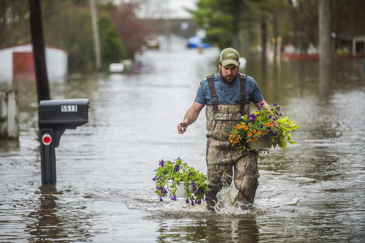 Tyler Marciniak, of Grand Rapids, carries hanging plants through floodwaters as he helps his father, Tom Marciniak, assess the damage to his home on Red Oak Drive on Wixom Lake, Tuesday, May 19, 2020, in Beaverton, Mich. (Katy Kildee/Midland Daily News via AP)