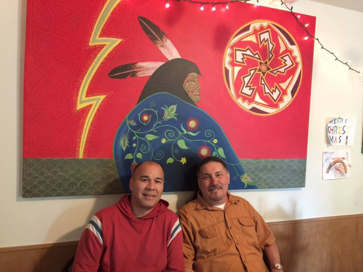 """""""Faith Keeper"""" Mixed media painting on canvas by the artist Roger Sosakete Perkins. Left to right: Roger Sosakete Perkins, Sosakete Perkins' cousin Jack Martin in front of painting in artist's studio. (Photo courtesy of Roger Sosakete Perkins)"""