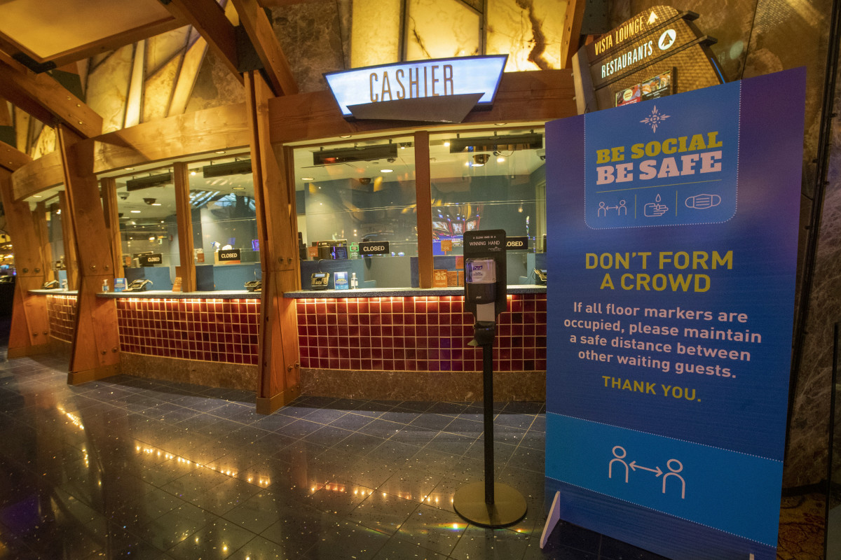 A hand sanitizer station and a sign asking guests to follow proper social distancing and sanitation measures are seen near the cashier station on the casino floor at the Mohegan Sun, Thursday, May 21, 2020, in Uncasville, Conn. Connecticut's two federally recognized tribes, Mashantucket Pequot and Mohegan tribes, said they're planning to reopen parts of their southeastern Connecticut casinos on June 1, despite Gov. Ned Lamont saying it's too early and dangerous. (AP Photo/Mary Altaffer)