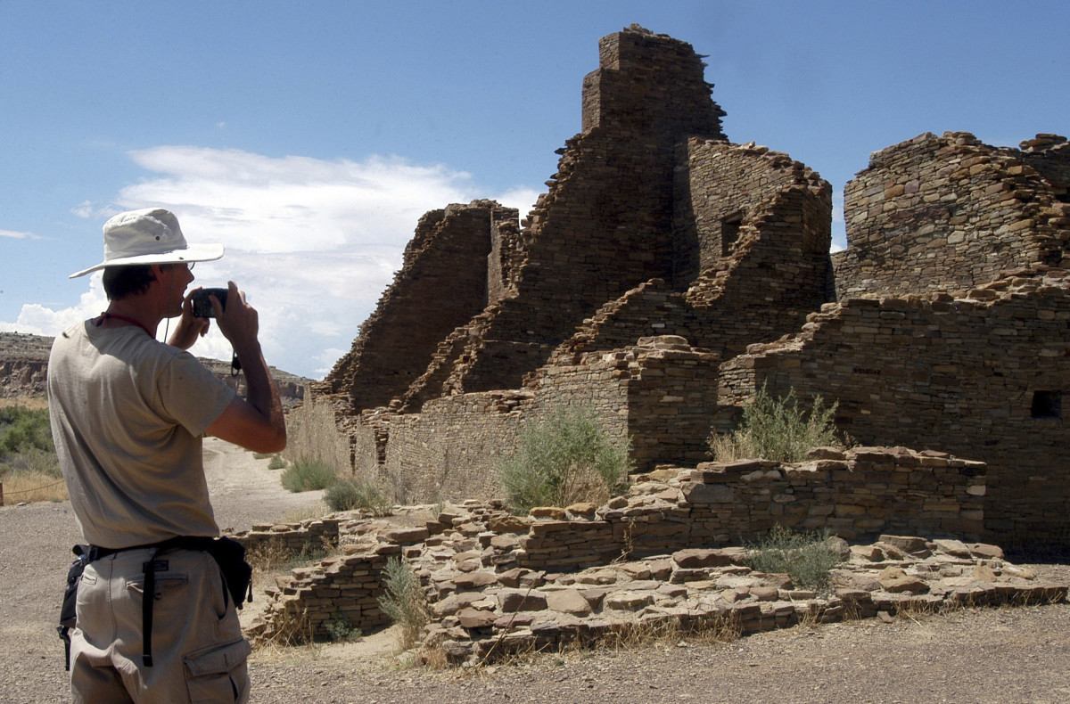 In this Aug. 10, 2005, file photo, tourist Chris Farthing, from Suffolks County, England, takes a picture of Anasazi ruins in Chaco Culture National Historical Park in New Mexico. U.S. Interior Secretary David Bernhardt says he'll extend the public comment period on a contested plan that will guide oil and gas drilling and other development in an area of New Mexico that includes a national park and locations important to Native American tribes. (AP Photo/Jeff Geissler, File)
