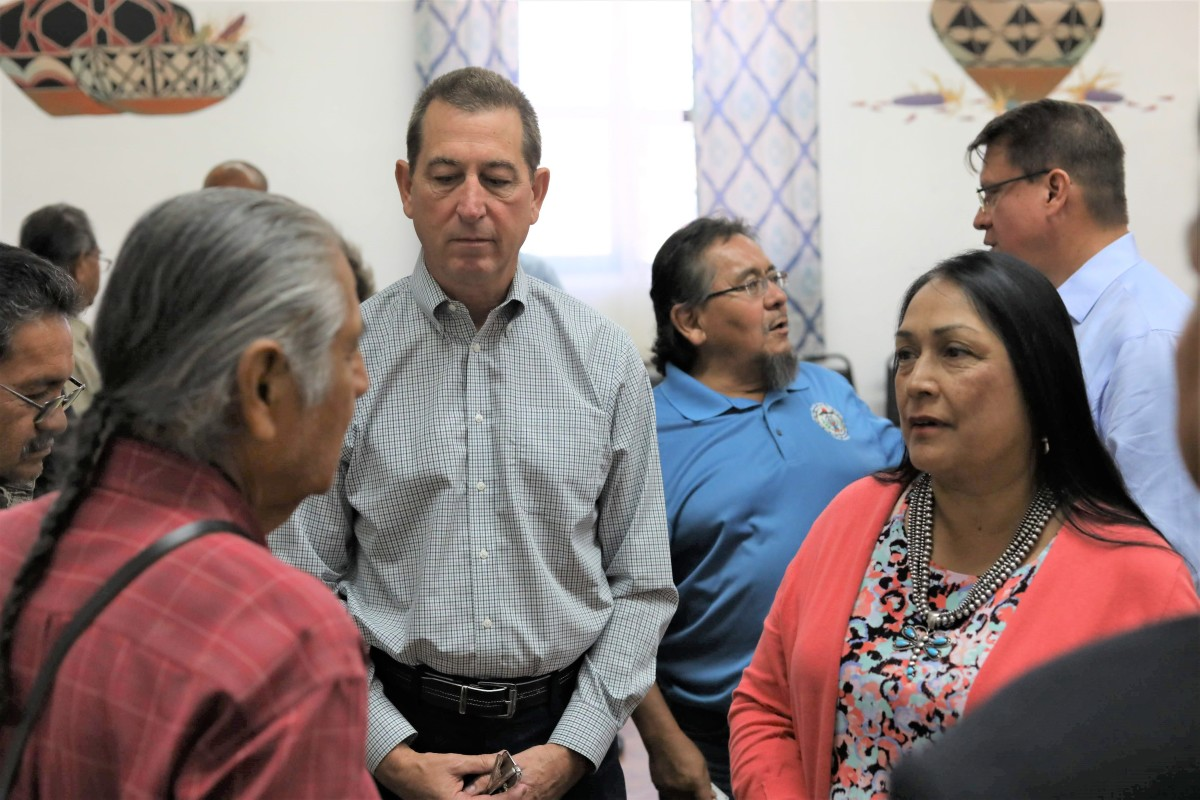 Pictured: Comptroller of Currency Joseph Otting and NAFOA Board President Cristina Danforth speak with tribal leaders during a community bus tour through Pueblo communities in August 2019.