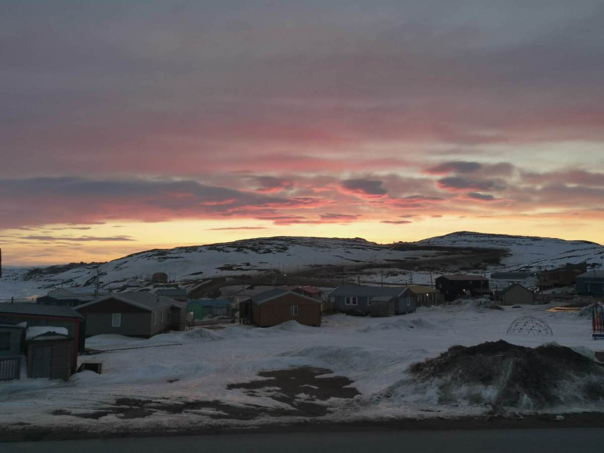 In this May 7, 2020 photo provided by Aaron Watson, the sun sets over Iqaluit, the capital of Nunavut territory in far north Canada. Iqaluit has a population of about 7,000 people, many of whom are Inuit. Watson says, so far, there are no cases of coronavirus in the town. (AP Photo via Aaron Watson)