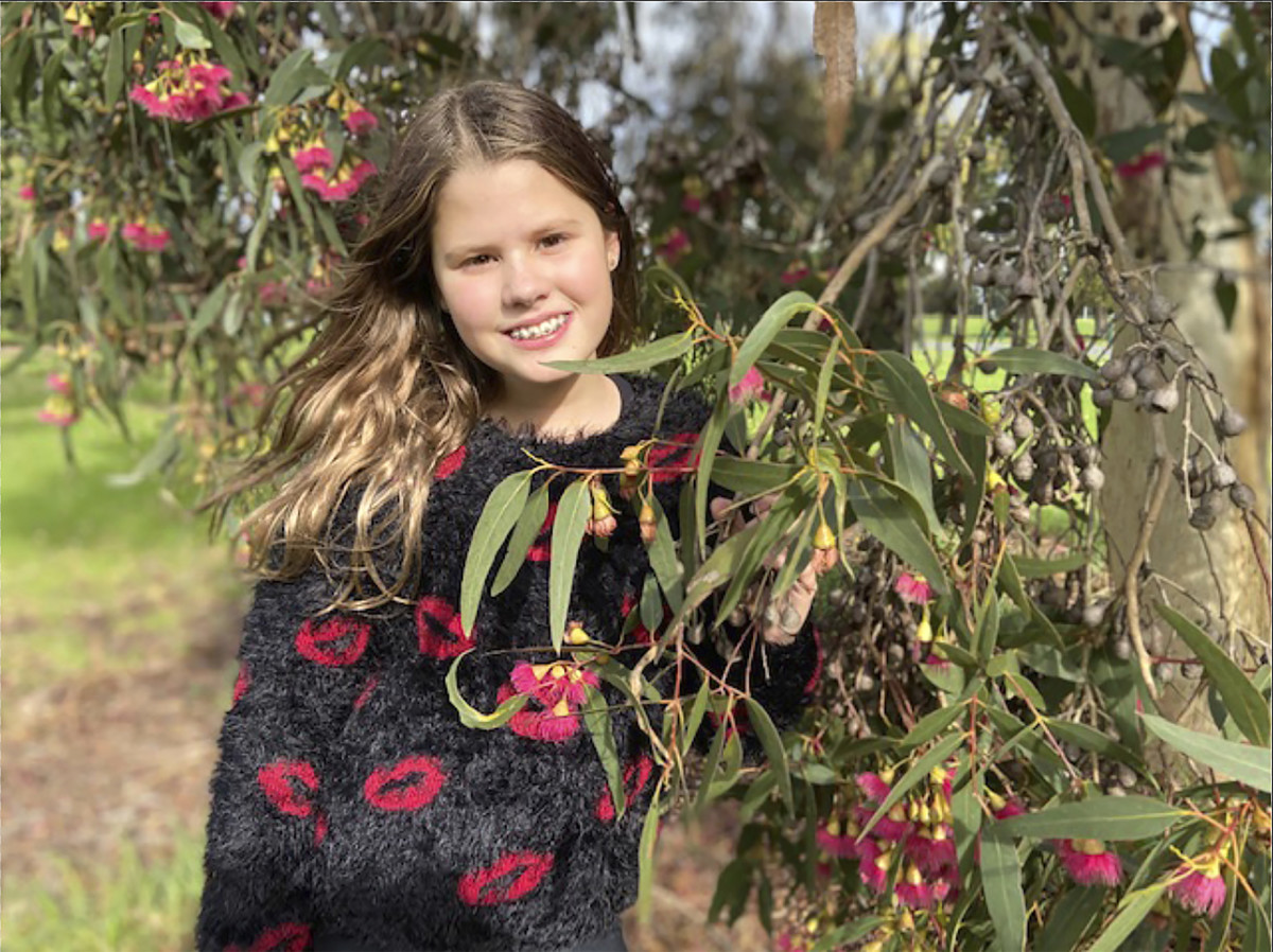 In this photo provided by her family, Niki Jolene Berghamre-Davis, age 11, stands next to a red flowering gum tree in Port Melbourne, Australia, on April 30, 2020. While sad about all the people lost to the virus pandemic, Niki is hopeful that the shutdowns are teaching the world how to live in ways that will help the environment. (Anna Berghamre via AP)