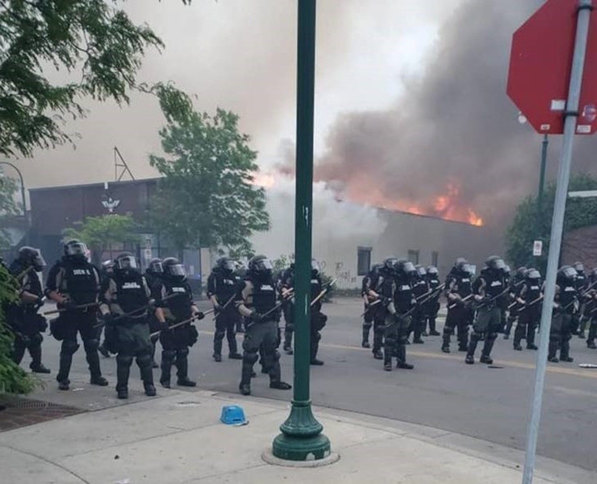 The Migizi Communications building burns in the background Friday morning in south Minneapolis. (Photo courtesy Melissa Olson)
