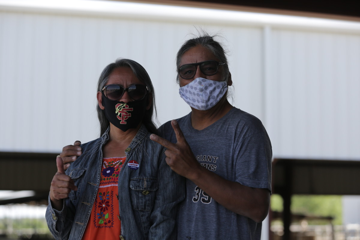 """Ali and Kenneth White Horse pose for a photo after voting in the Democratic primary on Tuesday, June 2, 2020, in Santa Fe, New Mexico. Ali White Horse, a school teacher, wore a mask and an """"I voted"""" sticker leaving the polling place, which sits on the edge of the country's rodeo grounds. Inside, poll workers wore masks and distributed hand sanitizer to prevent the spread of COVID-19. (AP Photo/Cedar Attanasio)"""