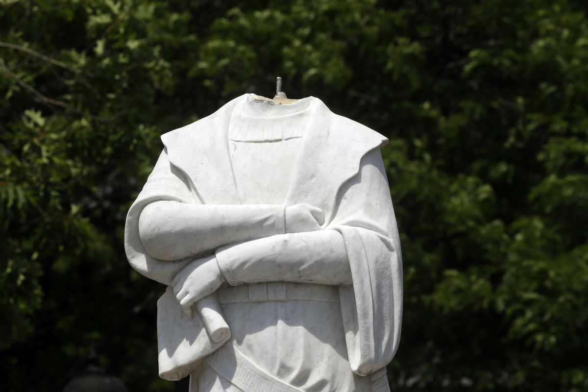 In this file photo dated Wednesday, June 10, 2020, a damaged Christopher Columbus statue stands in a waterfront park near the city's traditionally Italian North End neighborhood, in Boston, USA., after the statue was found beheaded Wednesday morning. Statues of the 15th-century explorer and the Spanish conquistadors who followed him and colonized much of the Americas have not become targets for demonstrators in Spain and USA. The death of George Floyd at the hands of police and Minneapolis, USA, has sparked a re-examination of injustices and inequalities in the fabric of many societies, often symbolized in statues of historical figures have become the focus of protest around the world. (AP Photo/Steven Senne, FILE)