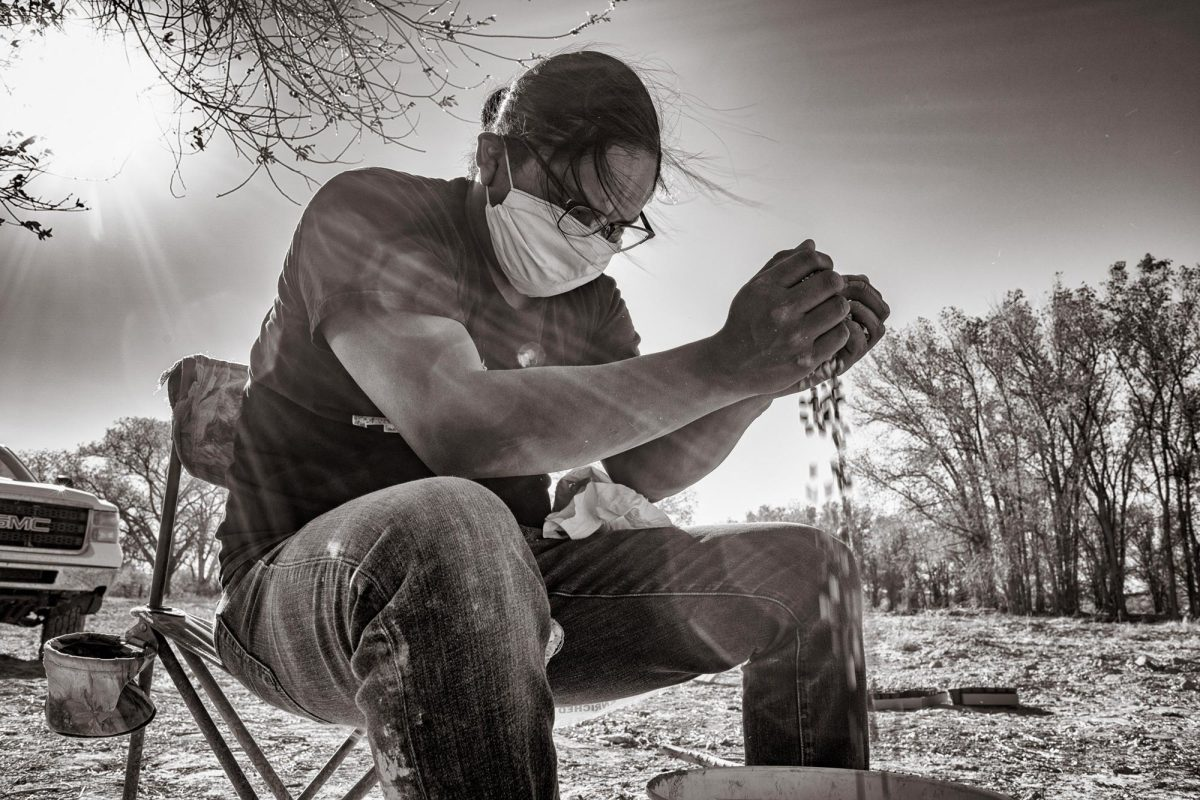 Eliseo Curley, Zefren Anderson's clan cousin, winnows blue corn grains through his hands at the farm where he and Anderson are planting. (Photo by Don J. Usner, Searchlight New Mexico)