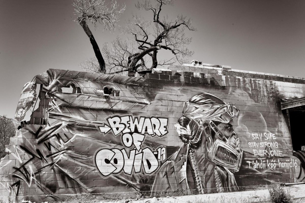 A mural in Shiprock, depicting a man in traditional dress with a respirator, warns residents about COVID-19. (Photo by Don J. Usner, Searchlight New Mexico)