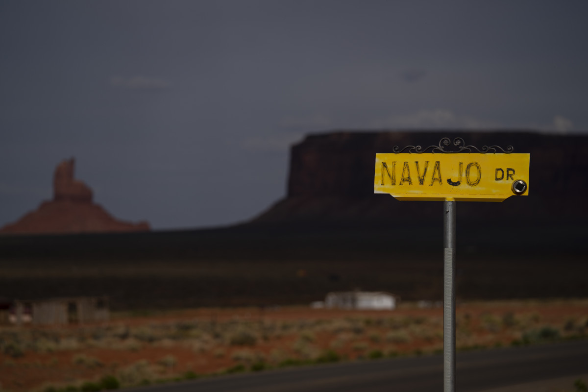 A sign for Navajo Drive is seen against a cloud-darkened Sentinel Mesa in Oljato-Monument Valley, Utah on the Navajo Reservation on April 30, 2020. The reservation has some of the highest rates of coronavirus in the country. If Navajos are susceptible to the virus' spread in part because they are so closely knit, that's also how many believe they will beat it. (AP Photo/Carolyn Kaster)