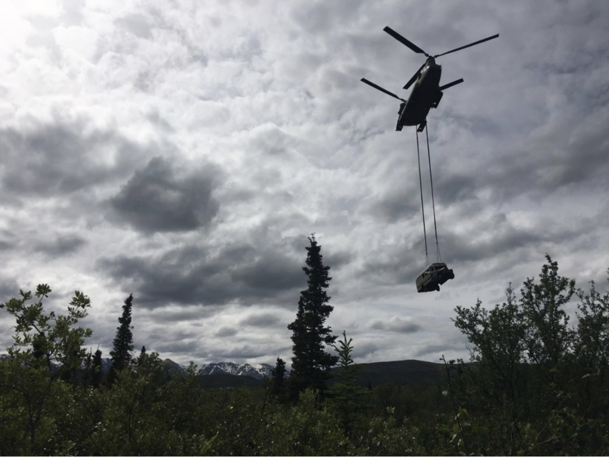 """The distinctive silhouette of a bus made famous by the """"Into the Wild"""" book and movie traverses the skies today near Stampede Trail, as an Alaska Army National Guard CH-47 Chinook helicopter moved it from its decades-long resting place west of the Parks Highway shortly before 1 p.m. ADT today. (Photo courtesy of the Department of Natural Resources, State of Alaska)"""