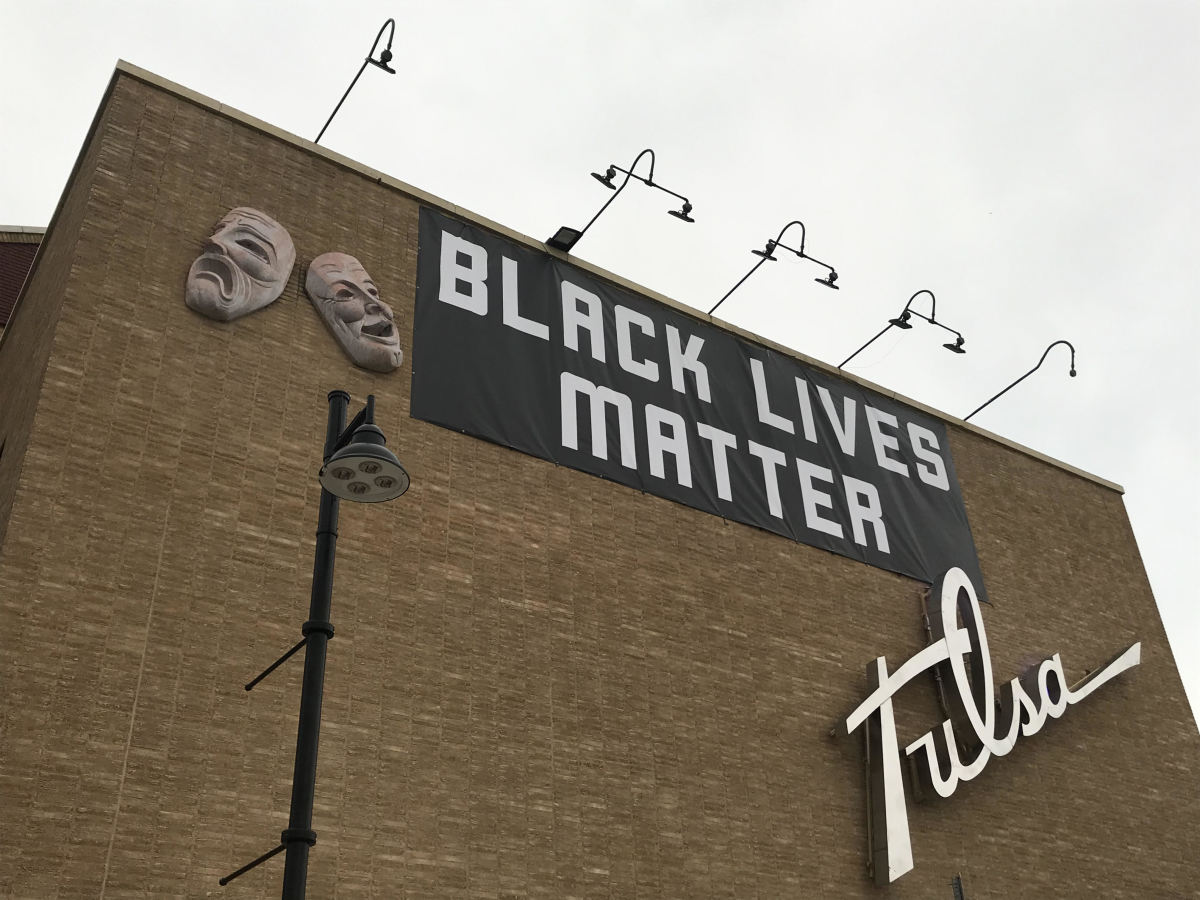 A Black Lives Matter banner hangs from the theater formerly known as Brady Theater, named for a founder of Tulsa a member of the KKK, just west of the Greenwood District of Tulsa, Oklahoma. (Photo by Graham Lee Brewer)