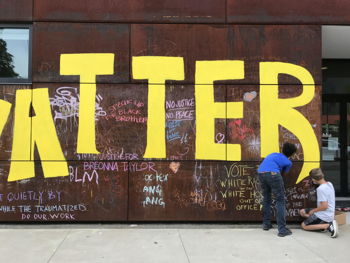 Two young boys chalk their own messages onto a Black Lives Matter mural on an arts building Friday near downtown Tulsa, Oklahoma. (Photo by Graham Lee Brewer)
