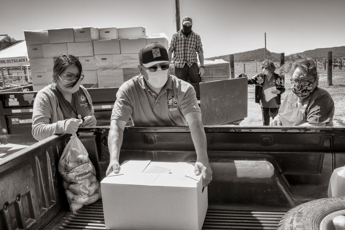 Sam Bryant of the Southwest Indian Foundation in Gallup loads a box of groceries into a pickup on the Navajo Nation at Oak Springs, Arizona. (Photo by Don J. Usner, Searchlight New Mexico)
