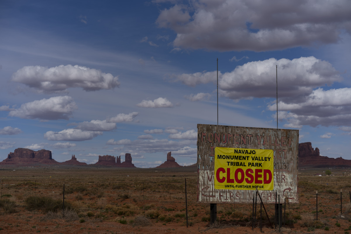 """A sign reads """"Navajo Monument Vally Tribal Park Closed Until Further Notice"""" posted at the entrance of Monument Valley in Oljato-Monument Valley, Utah, on the Navajo reservation April 19, 2020. (FILE: AP Photo/Carolyn Kaster)"""