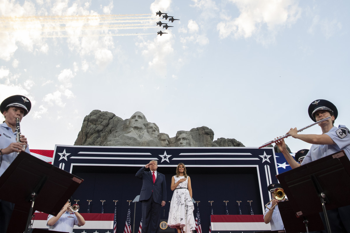 President Donald Trump, accompanied by first lady Melania Trump, stands during the national anthem with a flyover by the U.S. Navy Blue Angles at Mount Rushmore National Memorial, Friday, July 3, 2020, near Keystone, S.D. (AP Photo/Alex Brandon)