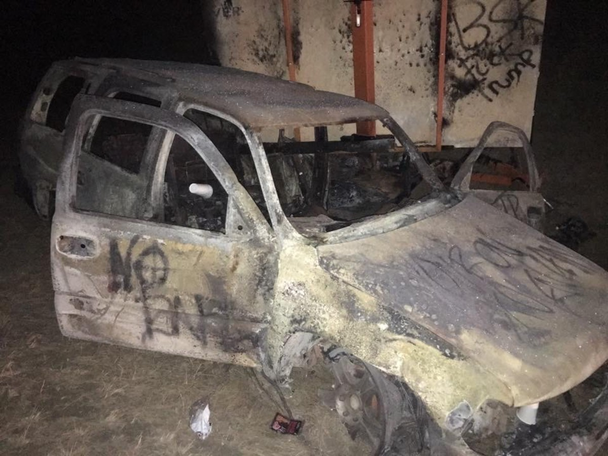 Burnt out car near bridge where water protectors clashed with law enforcement (Photo by Kolby KickingWoman)