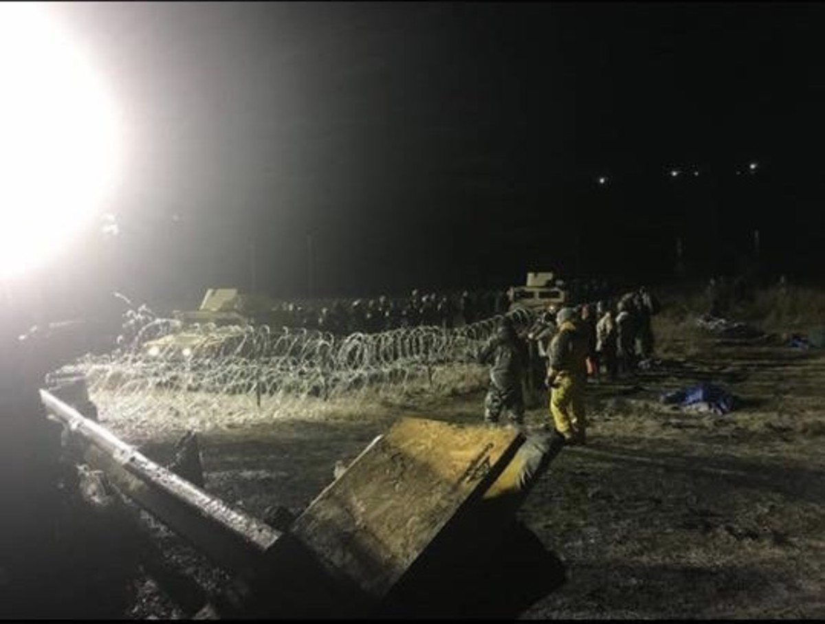 Water protectors stand near barb-wired fence in aftermath of law enforcement spraying demonstrators with tear gas, water cannons and rubber bullets (Photo by Kolby KickingWoman)