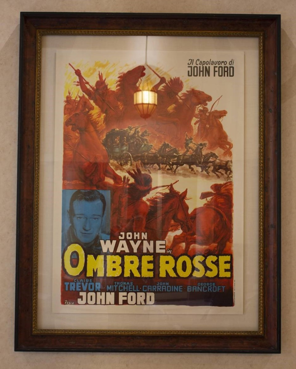 "A movie poster for John Wayne's film ""Ombre Rosse"" (known as ""Stagecoach"" in the U.S.) is in the lobby of the cinema school. In the film, Wayne's character crosses through Apache territory in a stagecoach. This is the film many credit with making him famous. (photo by Natasha Brennan)"
