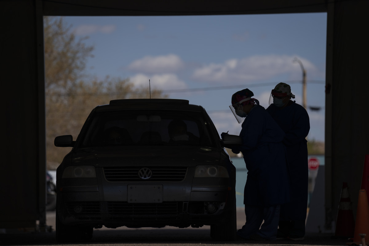 In this April 20, 2020, photo, Dr. Diana Hu, left, and a colleague wear personal protective equipment (PPE) as they work in the COVID-19 screening and testing tent in the parking lot at Tuba City Regional Health Care on the Navajo Reservation in Tuba City, Ariz. . (AP Photo/Carolyn Kaster, File)