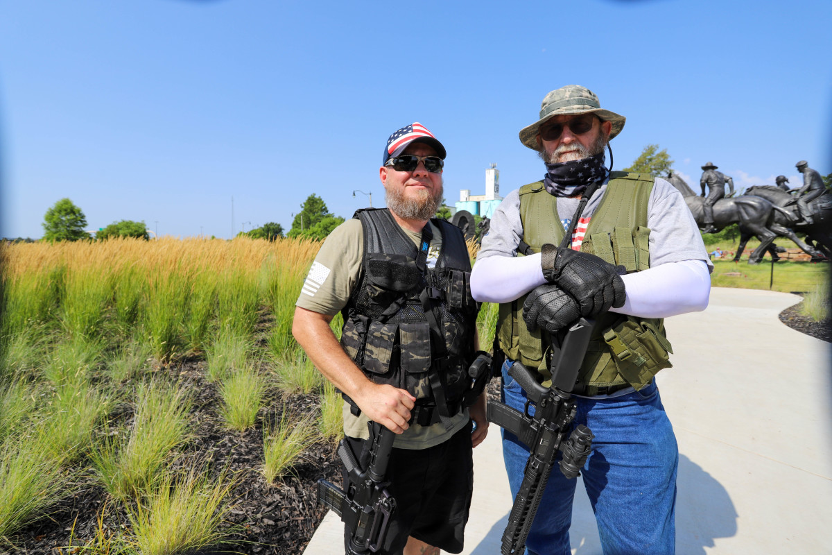 Robert (left) and Joe, who did not provide their last names, traveled from south Oklahoma to help protect the Centennial Land Run monument in Oklahoma City. They said, as they openly held their long rifles, they witnessed what happened in Minneapolis and St. Louis and they wanted to be prepared. (Photo by Ginny Underwood)