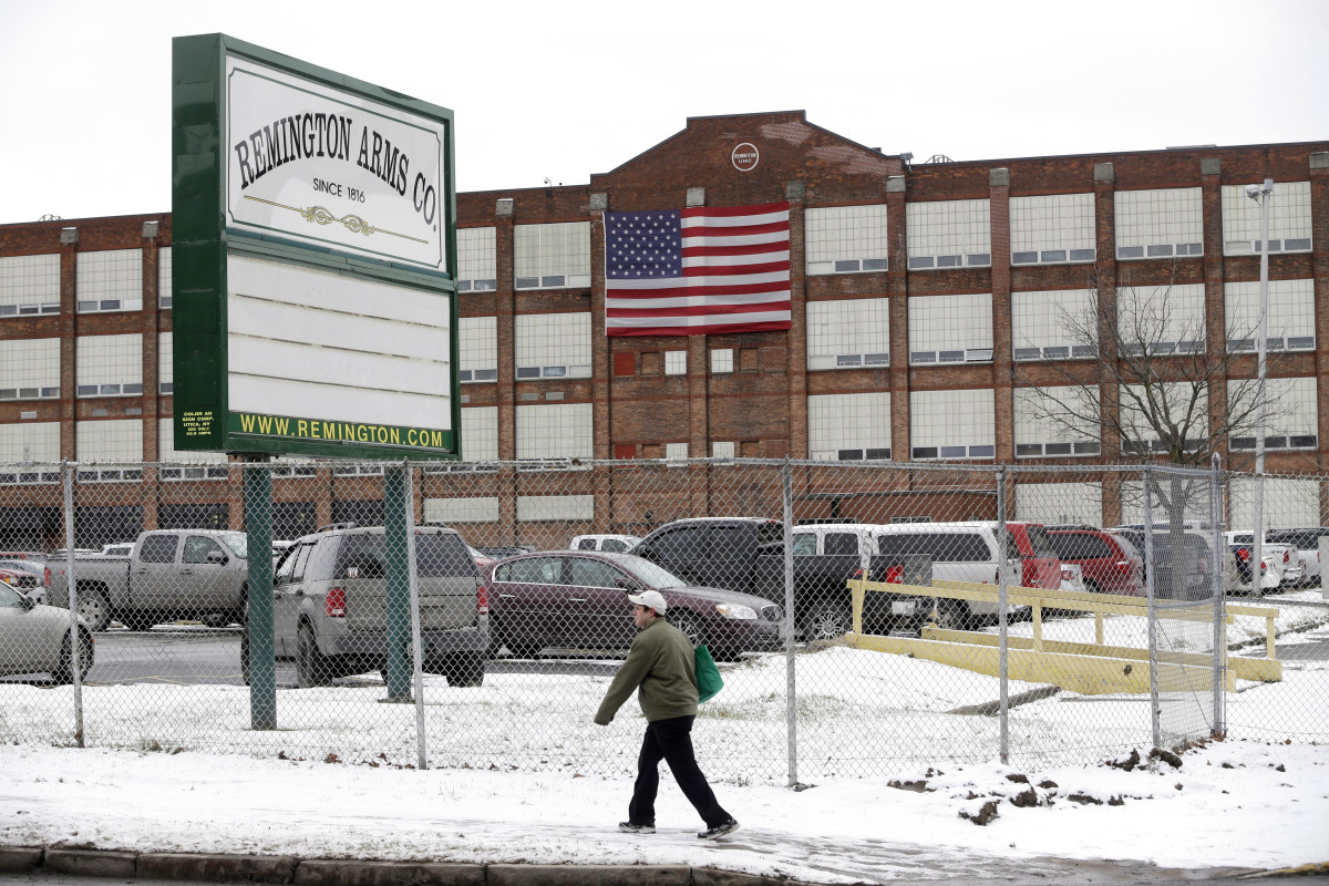 """FILE - In this Jan. 17, 2013, file photo, a man walks past the Remington Arms Company in Ilion, N.Y. The Ithaca Journal reports that the CEO Ken D'Arcy, wrote a letter Monday, March 23, 2020 to Governor Andrew Cuomo and President Donald Trump, offering """"approximately one million square feet of unused and available manufacturing space"""" at the Ilion plant for the manufacturing of hospital supplies in New York. (AP Photo/Mike Groll)"""