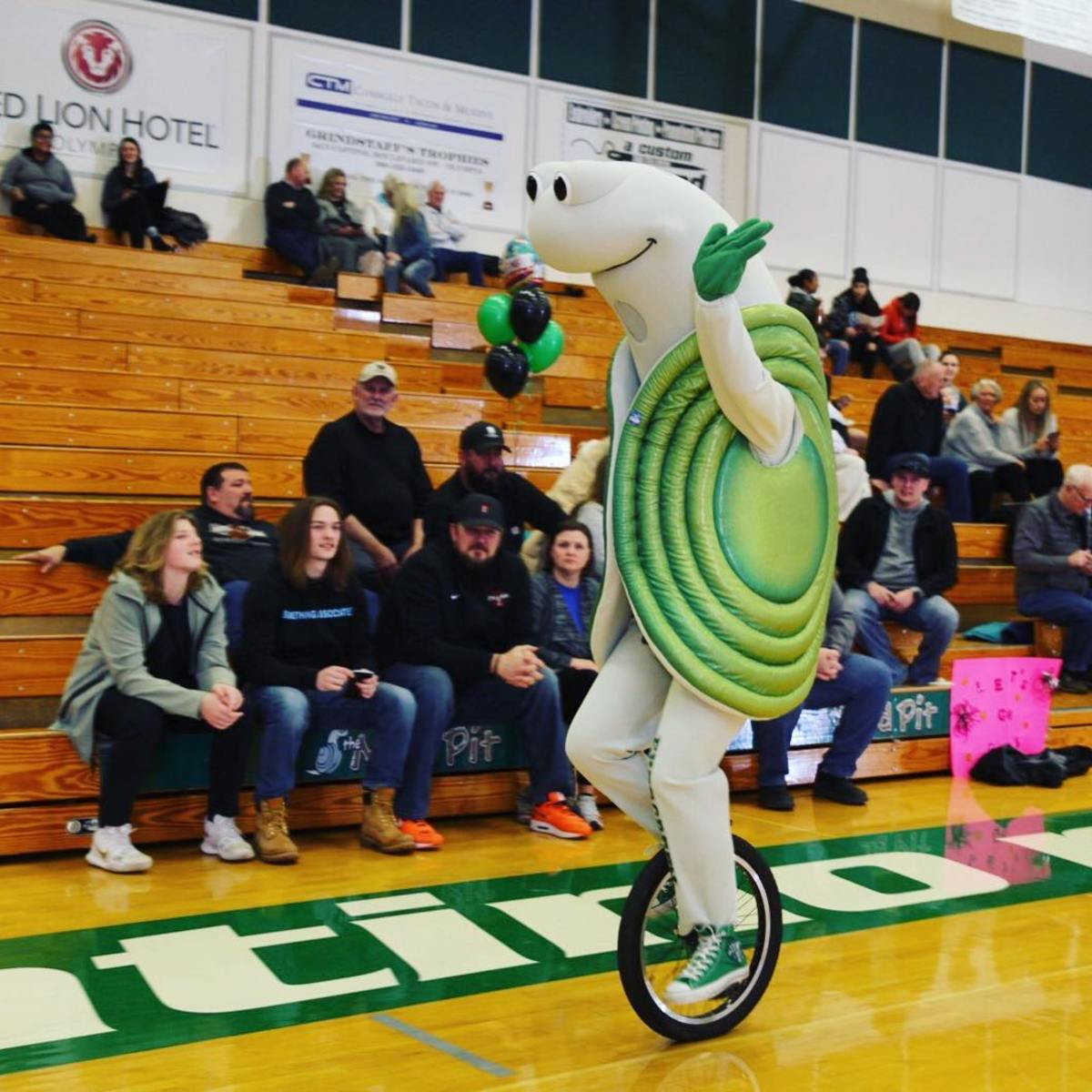 """""""Speedy the Geoduck"""" drives a unicycle at a basketball game in 2019. (Photo from The Evergreen State College, Facebook)"""