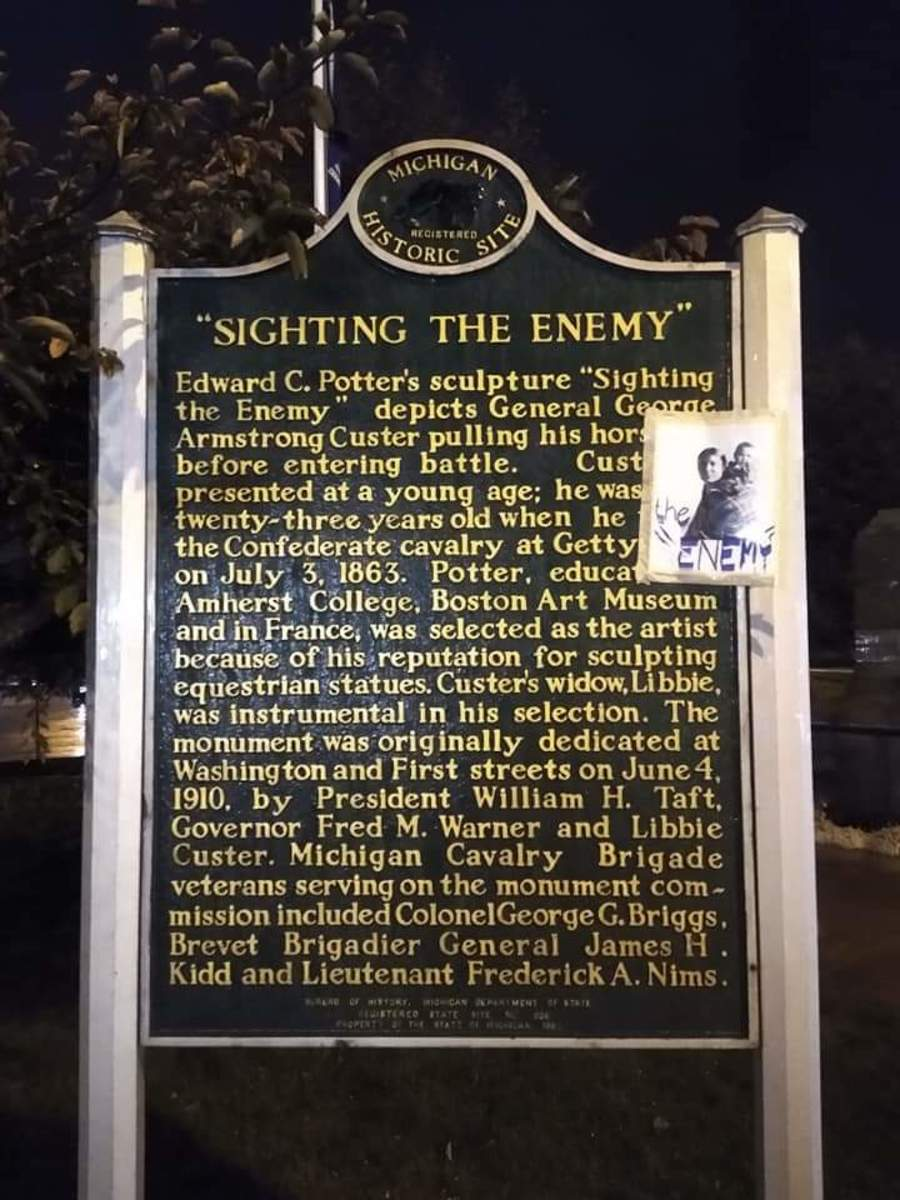 """Pictured: George Armstrong Custer plaque in St. Mary's Park, Monroe, Michigan. A photograph of a Cheyenne women and child, with the words """"The Enemy"""" written on it, was taped to the plaque commemorating the adjacent Custer statue, entitled """"Sighting the Enemy."""""""