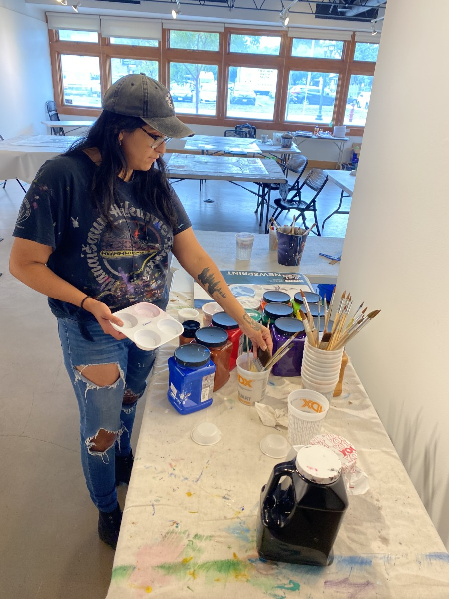 """Courtney Cochran, Anishinaabekwe, is the lead artist for an art installation set to go up in the fall of 2021 at the former site of an Indigenous homeless encampment called """"The Wall of Forgotten Natives."""" The installation features blocks of paintings that spell out """"Never Homeless Before 1492."""" (Photo by Dan Ninham for Indian Country Today)"""