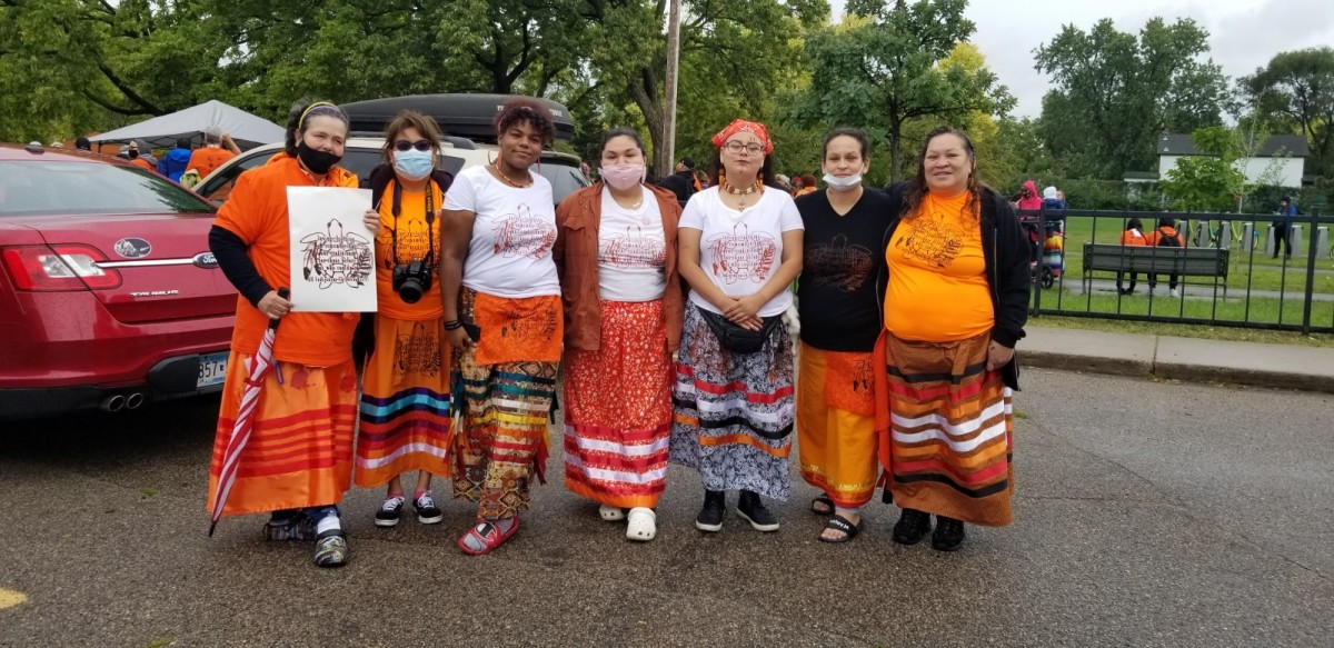 A special design for T-shirts and other clothing was created for a march of remembrance on Friday, Sept. 24, 2021, in Minneapolis, Minnesota, of boarding school victims. Among those who got the screened designs were, from left, Jolene Jones, Pam Johns, Simone Hunter, Isabel Diaz, Khaloni Fremont, Shantelle Neadeau and Jackie Neadeau. (Photo courtesy of Courtney Cochran)