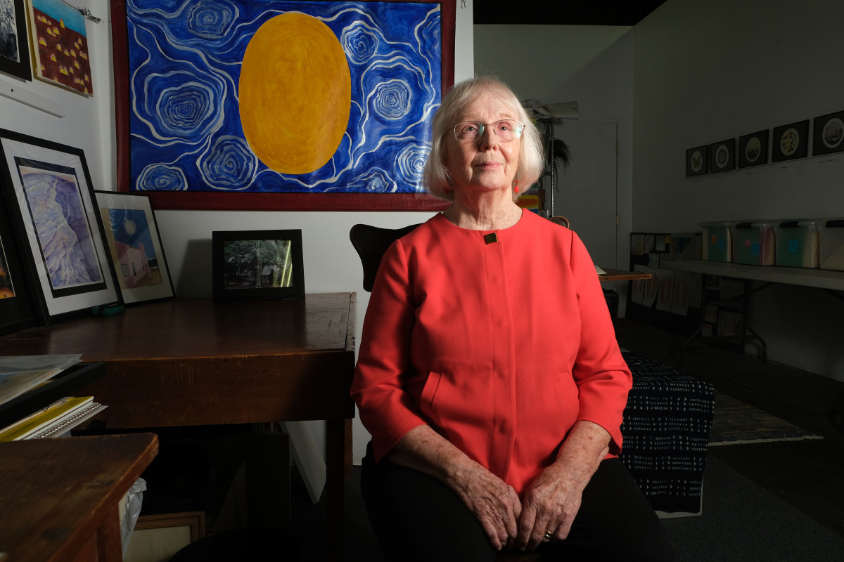 Jodine Grundy, sitting in her studio in Cincinnati, Ohio, in 2021, taught art and other subjects at St. Mary's Mission boarding school on the Colville Reservation in Washington state in 1966-1967 until a bad dream and uneasy feelings drove her to resign. Greatly influenced by her dreams, Grundy painted the photo behind her inspired by a dream. (Photo by Mary Annette Pember/Indian Country Today)