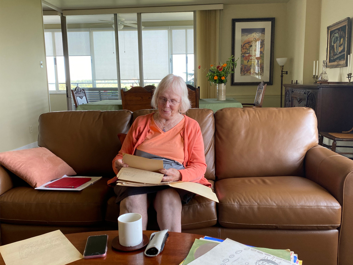 Jodine Grundy reads stories written by her students in 1966-67 when she taught at St. Mary's Mission Catholic boarding school on the Colville reservation in Washington state. She is shown here in her Cincinnati, Ohio, apartment in September 2021. (Photo by Mary Annette Pember, Indian Country Today)