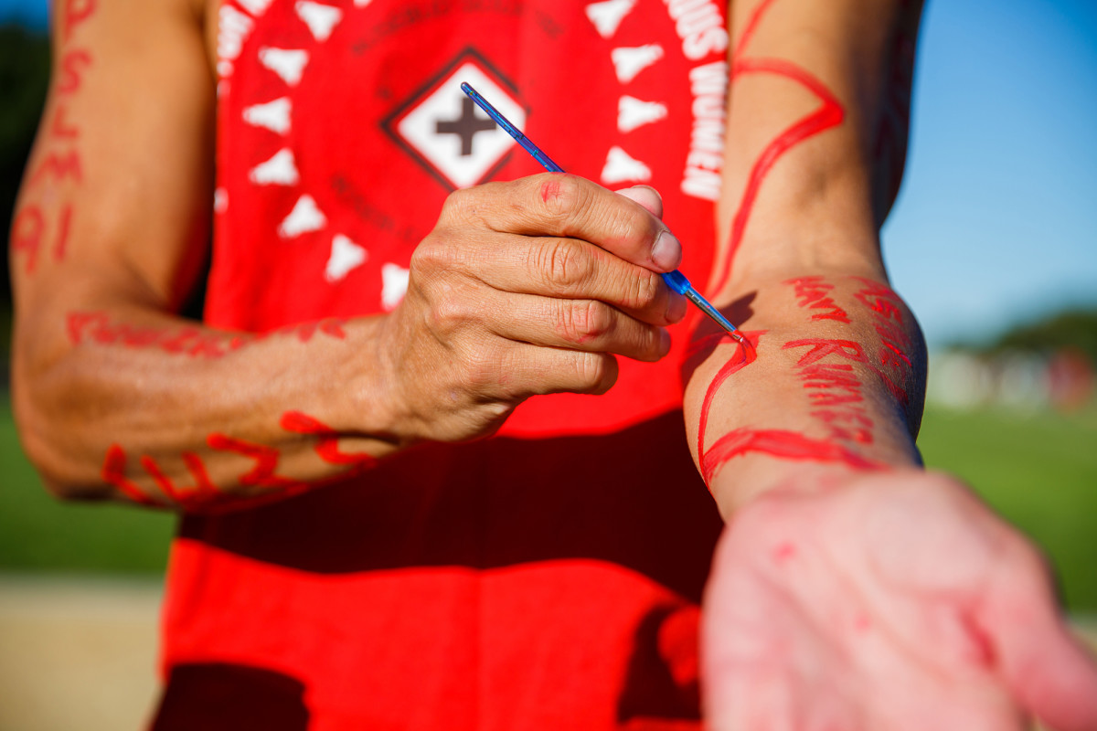 Duane Garvais-Lawrence paints the name of a missing Indigenous woman on his arm before starting a run around the National Mall in Washington, D.C. It was the last stop on a cross-country trip to raise awareness of the issue of missing and murdered Indigenous women. (Photo by Diannie Chavez/Cronkite News)