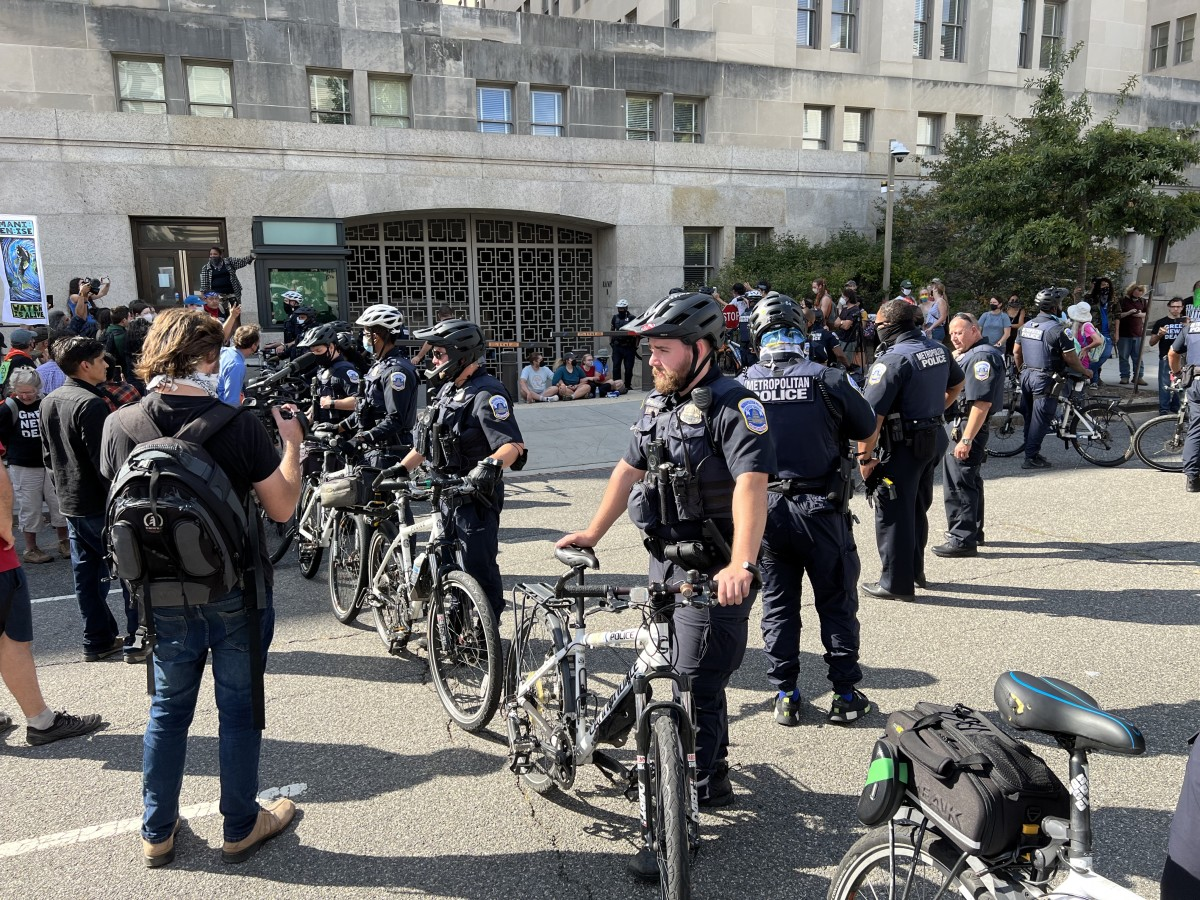 Officers of the Metropolitan Police made a path for vehicles on the east side of a building with their bikes so the vans could leave the Interior building. (Photo by Jourdan Bennett-Begaye, Indian Country Today)